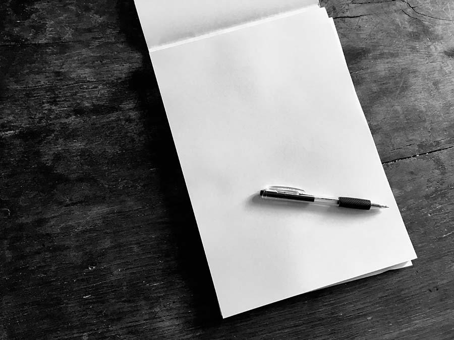 di parole e di promesse - blocco di fogli bianchi, con sopra una penna, appoggiati su una scrivania di legno